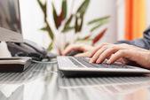 Hombre está escribiendo en el teclado y usando el ratón — Foto de Stock
