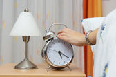 Alarm clock with woman  in bed — Stockfoto