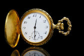 Gold pocket watch on a black background — 图库照片