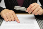 Businesswoman looking through a magnifying glass to contract — Stock Photo