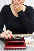 Woman watching sum on calculator with magnifying glass and cant — Stock Photo