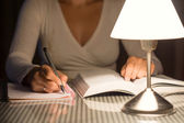 Woman is studying and take notes late at night — Stock Photo