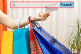 Girl showing shopping bags with search bar. Concept of on line s — Stock Photo