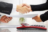 Businesswoman and businessman are handshaking and exchanging con — Stock Photo