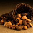 Assortment of nuts in basket on hesian background - Stock Photo