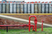 Fire hydrant water pipe in front of lpg gas bottles — Foto Stock