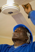 Construction Worker Fixing Ceiling Fan — Stock Photo