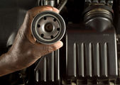South African or American hand holding oil filter with modern car engine background — Stock Photo