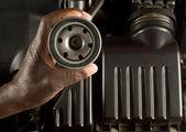 Mechanic holding oil filter — Stock Photo