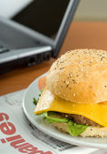Hamburger and laptop — Stock Photo