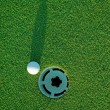 Golf ball on next to hole 3 - Stock Photo