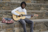 African busker on stone stairs — Stock Photo