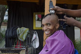 Smiling customer at African small haircut barber business — Foto Stock