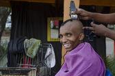 Sorrindo do cliente no negócio de corte de cabelo pequeno africano barbeiro — Foto Stock