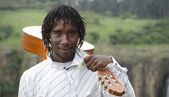 African busker with guitar on shoulder and ten rand note — Stock Photo