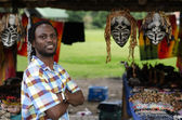 African curio salesman in front of ethnic masks — Stock Photo