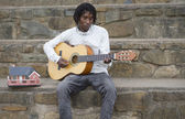 African busker playing on stone stairs — Stock Photo