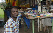 African curio salesman in front of ethnic items — Stock Photo