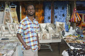 African curio salesman vendor in front of wildlife items — Stok fotoğraf