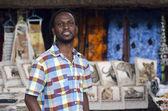 Afrika antika satıcısı satıcı etnik yaban hayatı öğelerin önünde — Stok fotoğraf