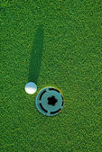 Golf ball on next to hole 3 — Stock Photo