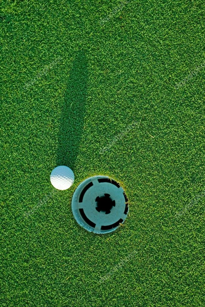 White golf ball on putting green next to hole with long shadow - from top down. — Stock Photo #18227915