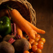 Thanksgiving cornucopia filled with autumn fruits and vegetables on wooden table. — Stock Photo #18230427
