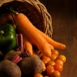 Stock Photo: Thanksgiving cornucopifilled with autumn fruits and vegetables on wooden table.