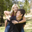 Piggyback girl on back in park — Stock Photo