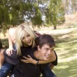 Stock Photo: Piggyback girl on back in park with grass