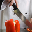 Chef Cutting Red Pepper - Stock Photo