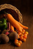Thanksgiving cornucopia filled with autumn fruits and vegetables on wooden table. — Stock Photo