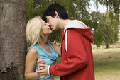Close up Couple kissing nest to garden tree — Stock Photo