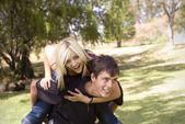 Piggyback girl on back in park with grass — Stock Photo