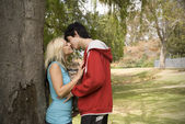 Couple kissing nest to garden tree — Stock Photo