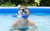 мальчик в бассейн в саду с маской и трубкой — Стоковое фото