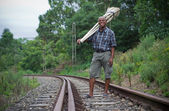 Stock photograph of South African entrepreneur small business broom salesman on railway line — Stock Photo