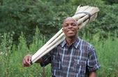 Fotografía stock de sonriente vendedor empresario sudafricano pequeños negocios escoba — Foto de Stock
