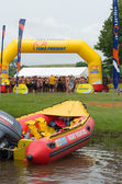 Surf rescue water life saving infatable boat with 2013 Midmar Mile swimmers in background — Foto Stock