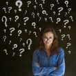 Thinking business woman with chalk question marks — Stock Photo #22303215