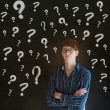 Thinking business man with chalk question marks — Stock Photo