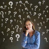 Thinking business woman with chalk question marks — Stock Photo