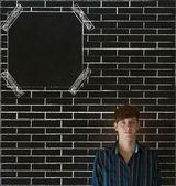 Business man, student or teacher on brick wall notice board blackboard background — Stock Photo