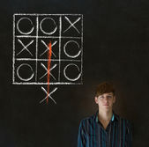 Thinking out of the box man on blackboard background — Stock Photo