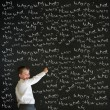 Writing boy dressed as business man with chalk questions — Stock Photo #24905309