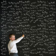 Writing boy dressed as business man with chalk questions - Stock Photo