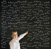 Pointage garçon déguisé en homme d'affaires avec des questions de craie — Photo