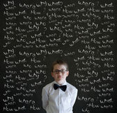 Thinking boy dressed as business man with chalk questions — Stock Photo
