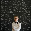 Thinking boy dressed up as business mwith chalk questions — Stock Photo #25016057
