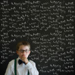 Thinking boy dressed up as business man with chalk questions — Stock Photo